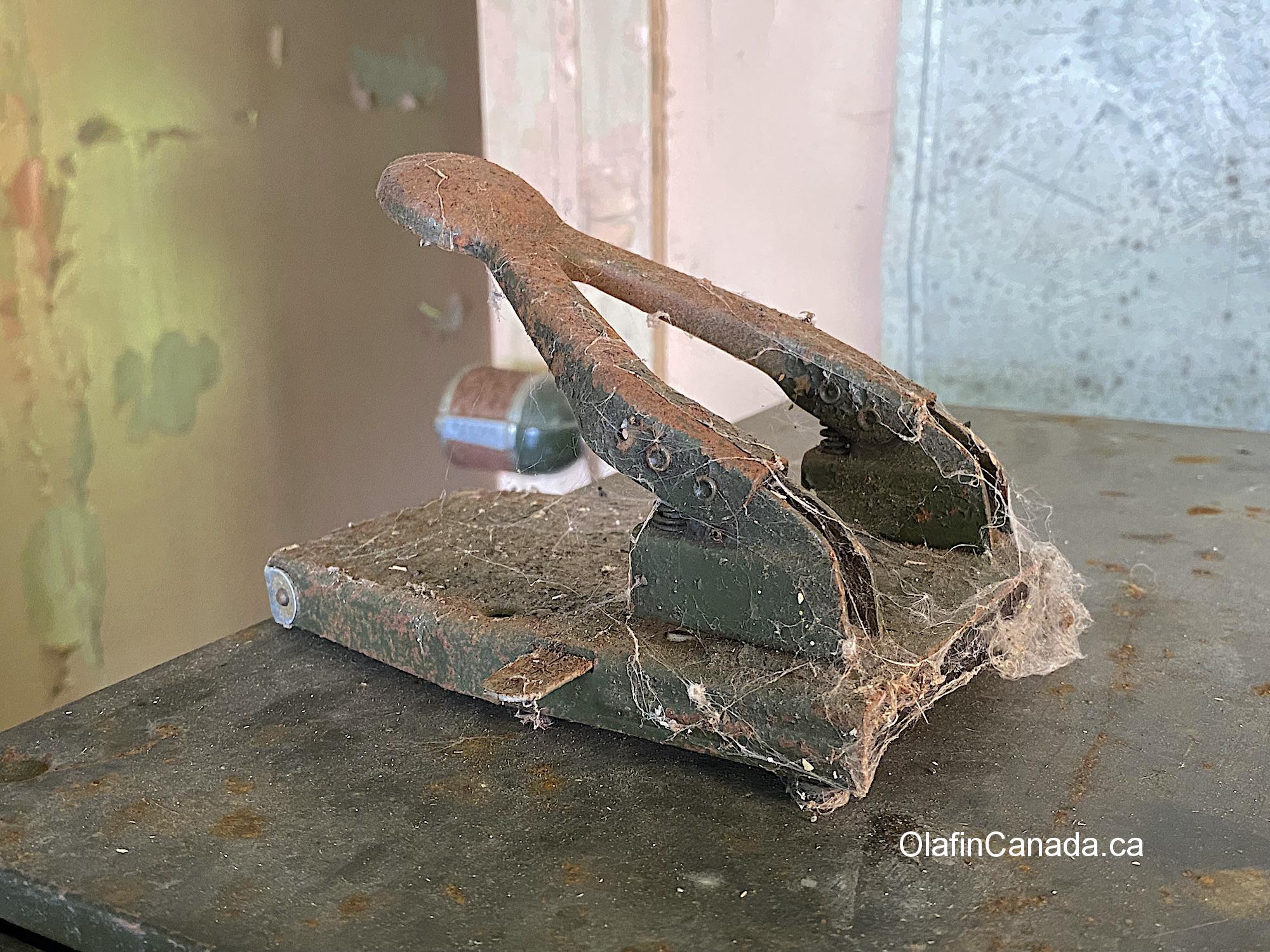 A hole puncher full of cobwebs in the office #olafincanada #britishcolumbia #discoverbc #abandonedbc #tallheocannery #bellacoola